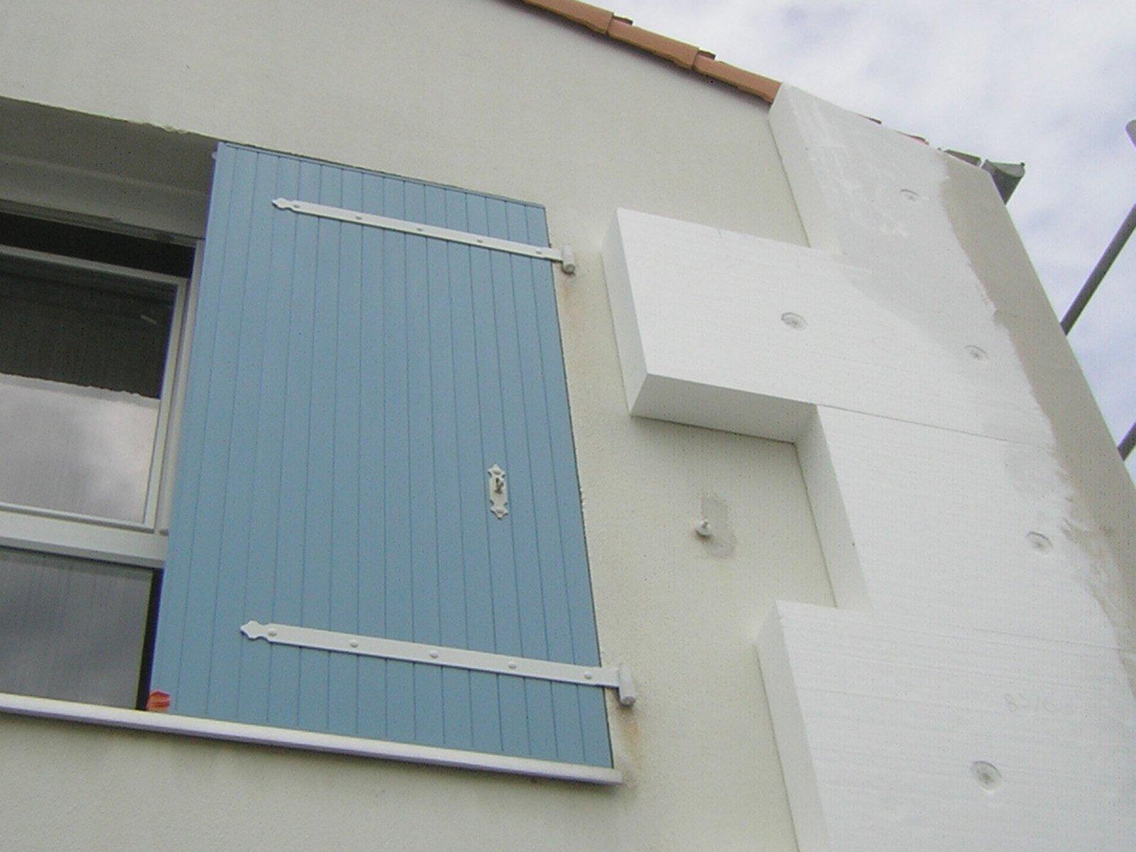 Isolation extérieure en cours sur la façade d'une maison avec volets bleus par ROGER SAS en Loire Atlantique